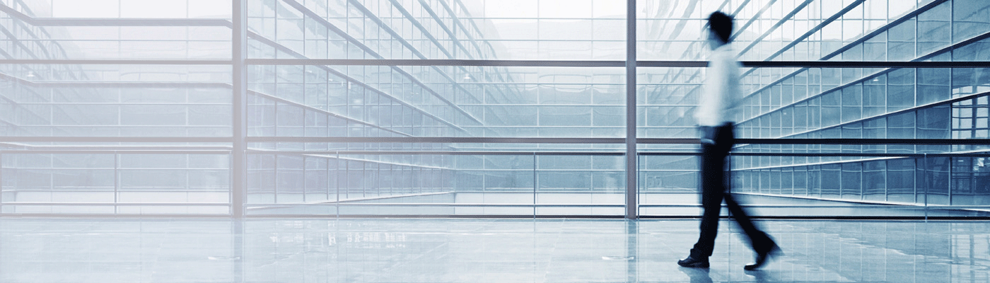 man-walking-through-hallway-with-windows
